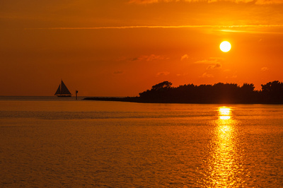 A spectacular sunset as the Skipjack Wilma Lee sails past the entrance to Silver Lake, Ocracoke, NC