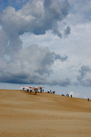 Afternoon thunderclouds were building over this group of hang gliders making for quite a contrast on the big dune.