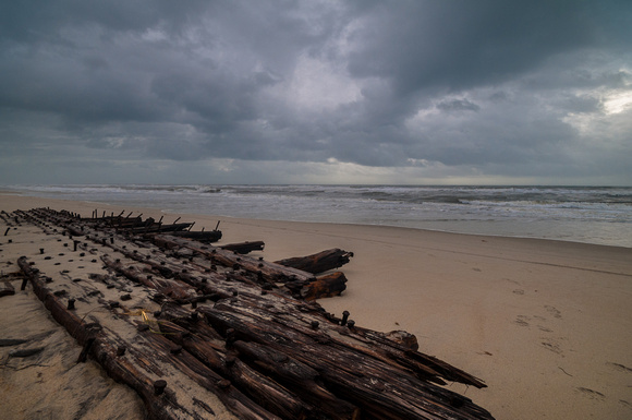 Shipwreck remains under a stormy sky